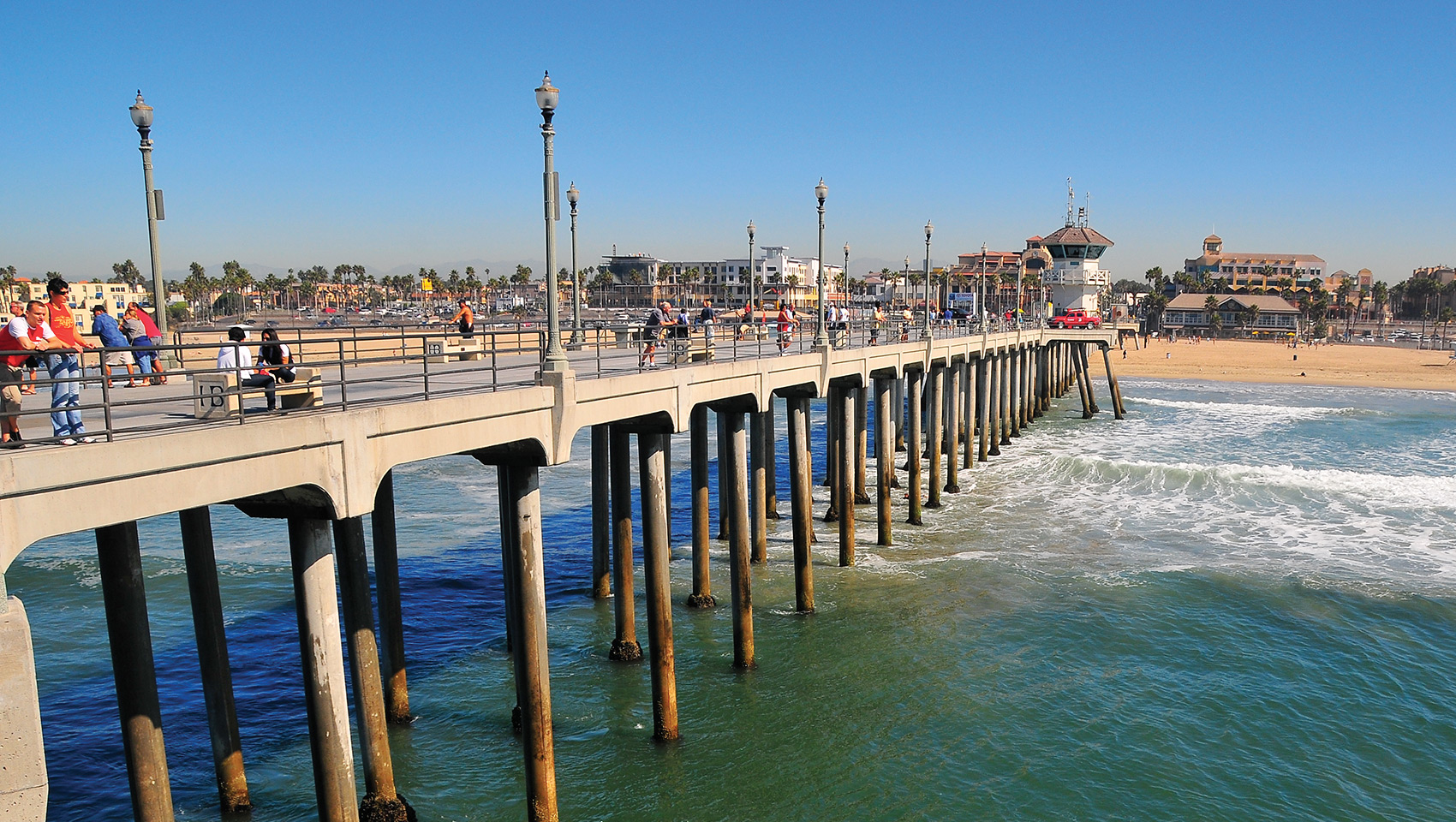 Huntington Beach Pier With Surfers Wading In The Water Below