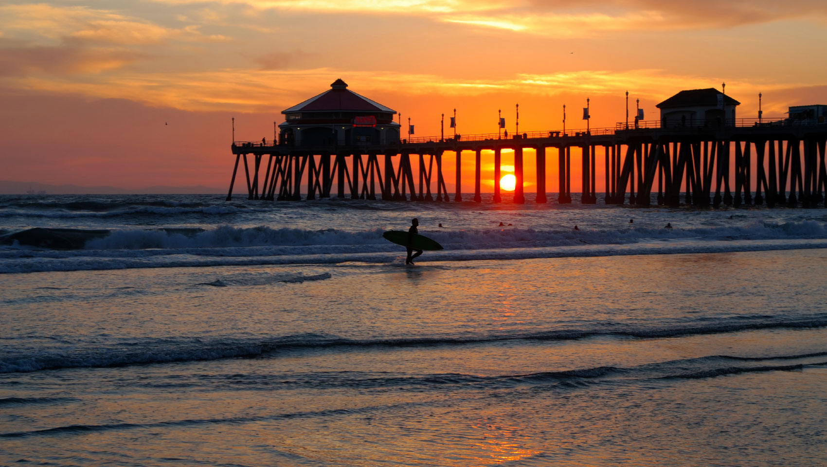 Huntington Beach Pier With A Surfer Walking At Sunset