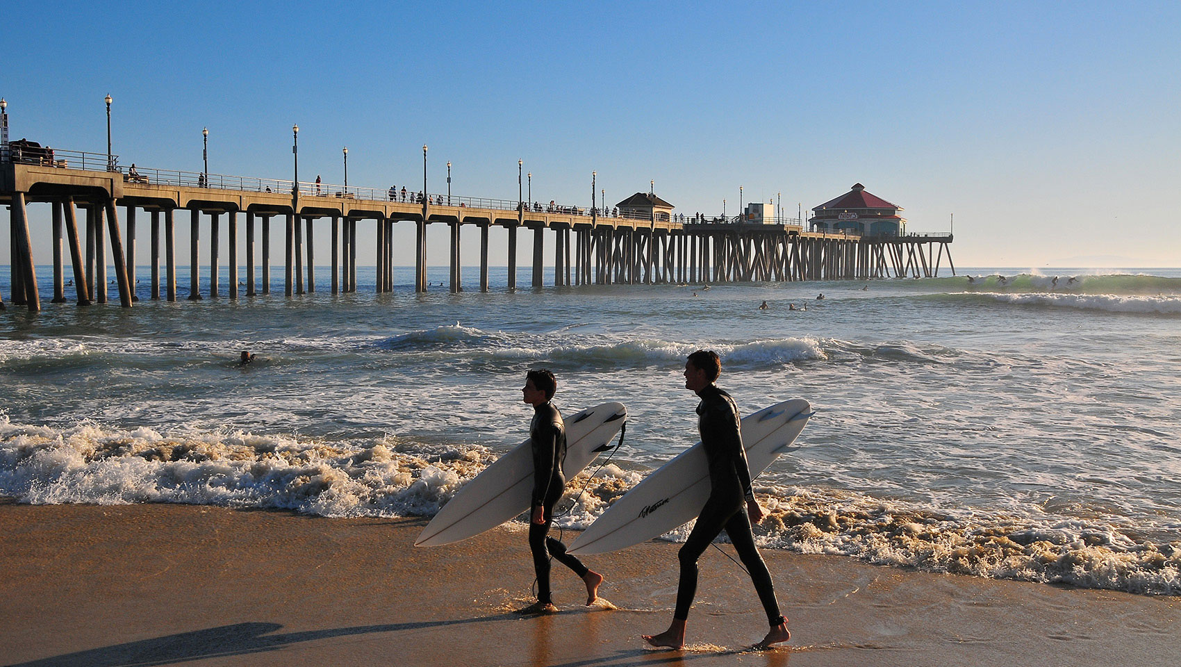 surfers walking with surfboards at huntington beach